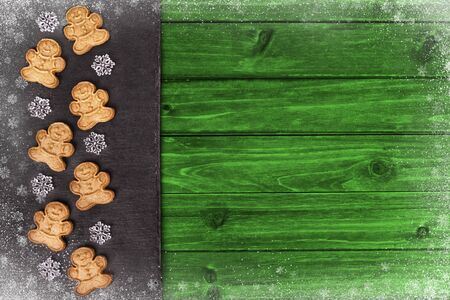 Gingerbread cookies and snowflakes in decoration on green wooden table, directly above.