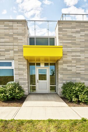 Modern primary school building architecture, door entrance. Sunny spring day.