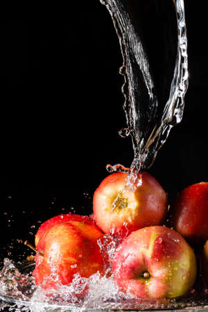 The few red apples lying on a silver top and falling water on a black background