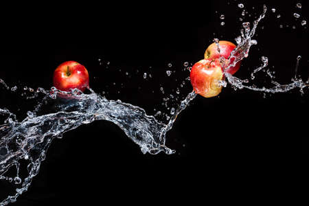 few red apples apple flying in space with the water on a black background