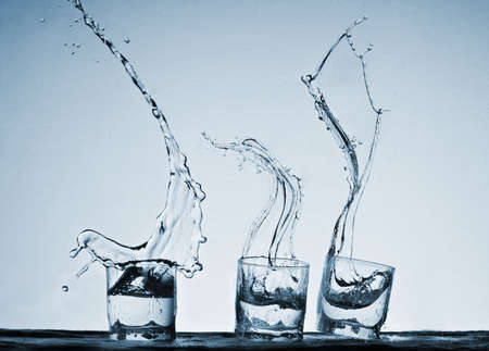 alcoholic drink: Big splash in glasses of alcoholic drink on a blue background