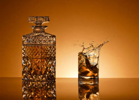 alcoholic beverage: Decanter with an alcoholic beverage on a gold background Stock Photo