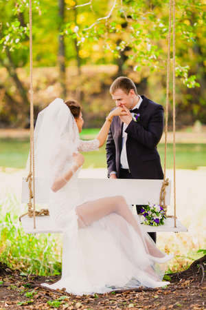 Bride portrait on a swing on a background of the autumn landscape near the river Stock Photo