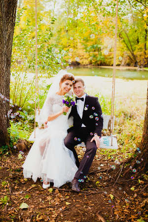 The bride and groom on a swing and flying bubbles