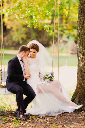 The bride and groom on a swing on a background of the autumn landscape