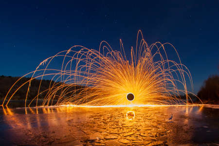 steel wool: Night winter landscape and sparks from the burning steel wool