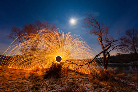 Night winter landscape and sparks from the burning steel wool
