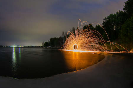 steel wool: Sparks from the burning steel wool on the frozen lake