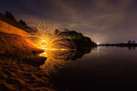 steel wool: Sparks from the burning steel wool on the river bank Stock Photo