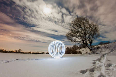 over the edge: Luminous sphere on a frozen lake and the light of the full moon