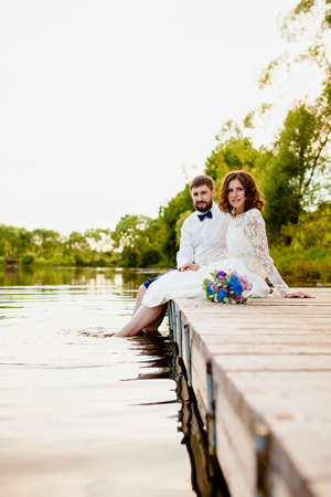 The bride and groom are sitting on a wooden pier near the pond at sunset