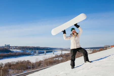 Young woman showing her snowboard as a white empty space