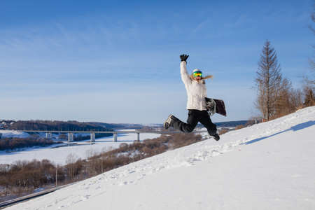 Young woman jumping with her snowboard Stock Photo
