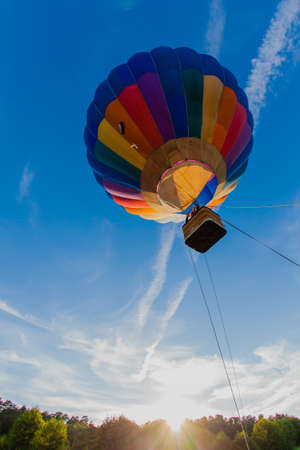 Colorful hot air balloon in blue sky at sunset