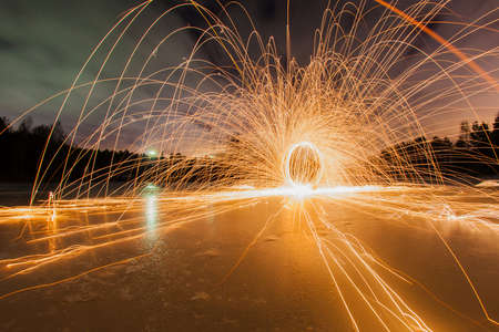 steel wool: Trajectories of burning sparks on the surface of frozen lake at the background of spring night landscape Stock Photo