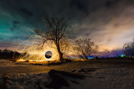 steel wool: Abstract picture with trajectories of burning sparks near the tree at the background of spring night landscape Stock Photo
