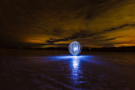 Futuristic glowing sphere on the surface of frozen lake at the background of spring night landscape Stock Photo