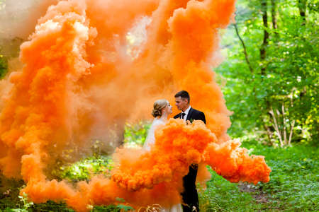 The bride and groom with the orange colored smoke at the background of summer forest