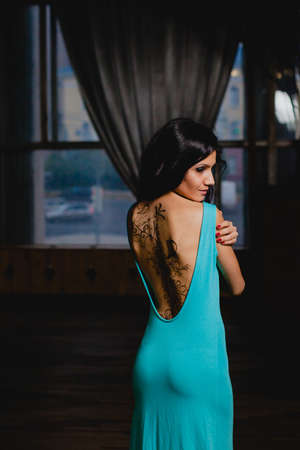 Slender brunette with henna ornaments drawn on her back