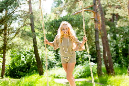 lag: Beautiful blonde woman swinging on the rope swing