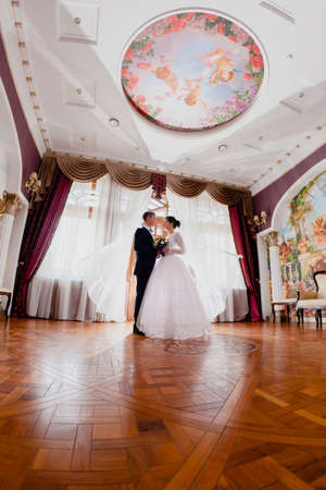 Wedding couple and curtains flying in the air Stock Photo