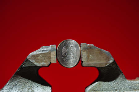 The coin in vise on the red background as a symbol of economic sanction against of Russia