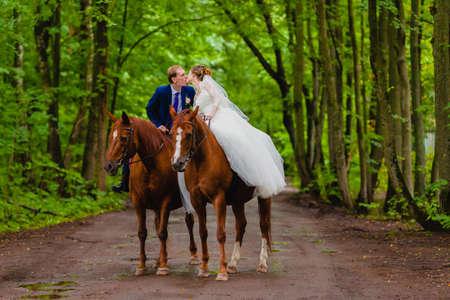 Beautiful newlyweds riding two horses