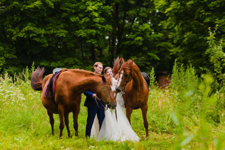 Beautiful newlyweds with two horses