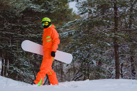 Snowboarder walking through the forest