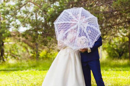 Beautiful couple newlyweds with the white umbrella