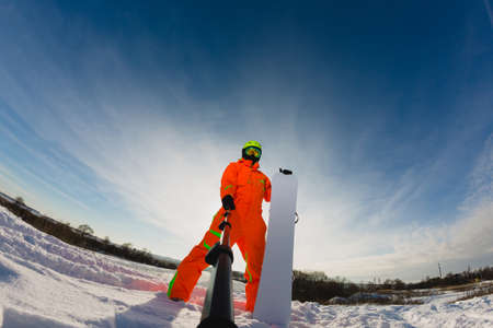 Snowboarder with the snowboard making a selfie
