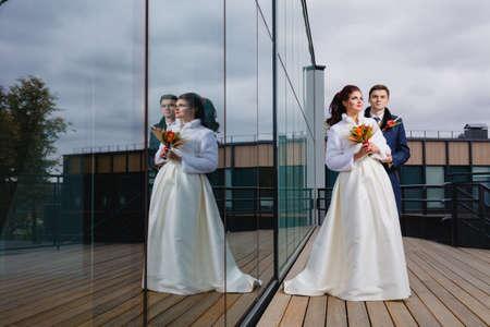 Beautiful couple newlyweds near the mirror wall