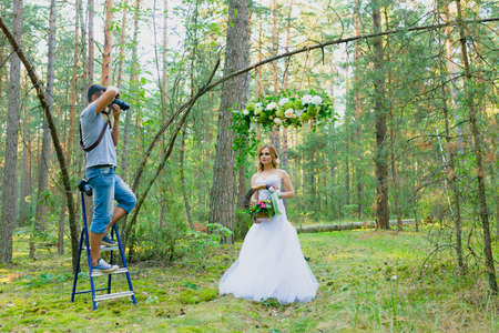 Wedding photographer using stepladder to make pictures of the bride