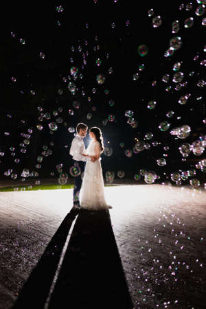 Couple of newlyweds in the darkness at the background of flash of light