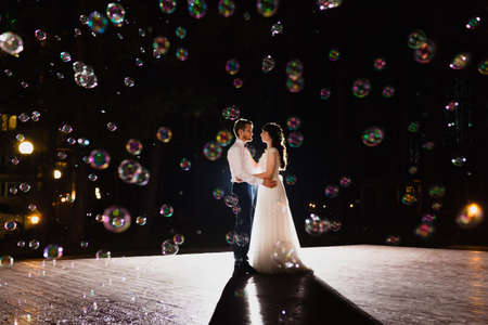 Couple of newlyweds and huge amount of bubbles are flying in the air Standard-Bild