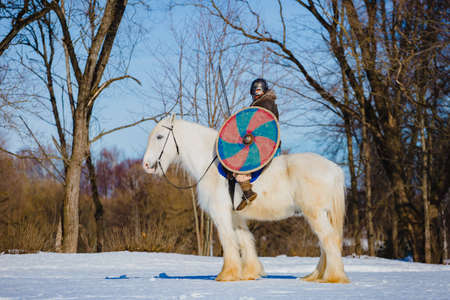 Man in suit of ancient viking riding big white horse