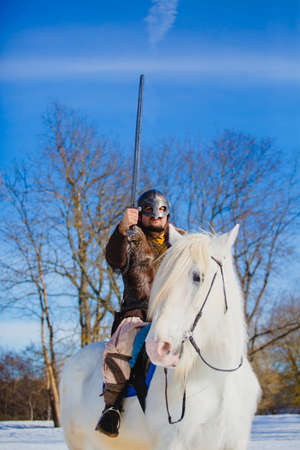 Man in suit of ancient warrior raising his sword