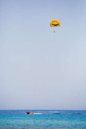 Three tourists flying on a yellow parachute with smiling face on it Stockfoto