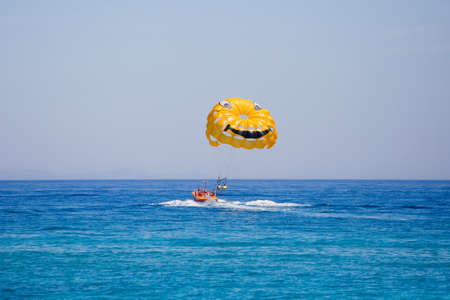 Couple of tourists flying on a yellow parachute with smiling face on it