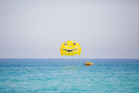 Woman flying on a yellow parachute with smiling face on it
