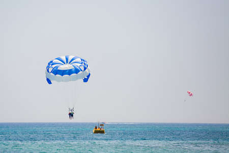 Couple of tourists flies on a blue and white parachute