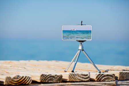 Smartphone on tripod making photo and video of sea landscape Archivio Fotografico