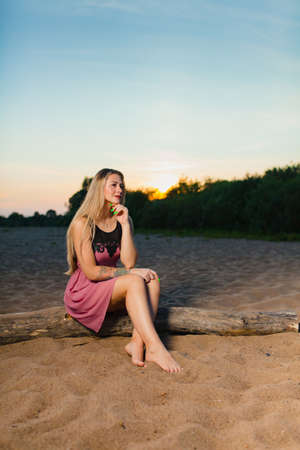 Portrait of the beautiful blond model with long hair on the sand beach