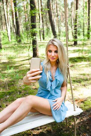 Beautiful blond woman in blue dress using smartphone to taking selfie