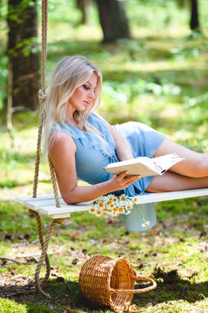 Beautiful blond woman in blue dress reading a book on a swing