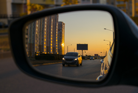 street, with sunset in the mirror of the car
