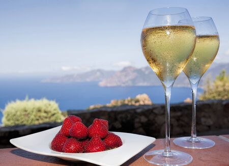 romantic drink in corsica with strawberries and white wine in two glasses and a view on the sea photo