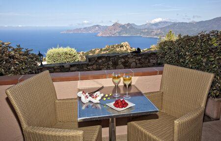 caballo bebe: copa romántica en Córcega con fresas y vino blanco en dos vasos y una vista sobre el mar