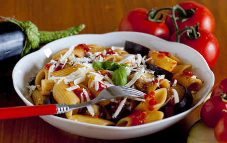 ricotta cheese: typical italian food: sicilian pasta, called Norma, with tomato, aubergines and ricotta cheese