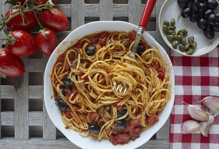 puttanesca: italian food: pasta with tomatoes, olives and capers, called puttanesca